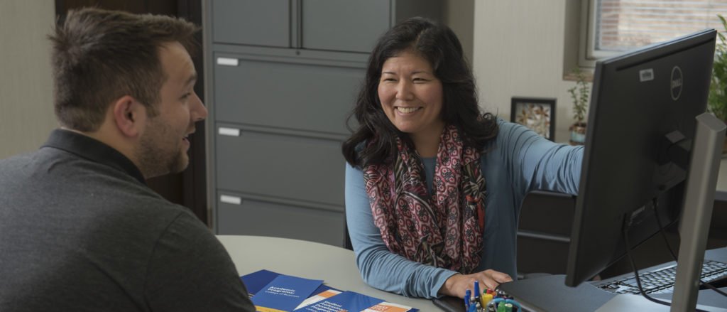 A UW-Eau Claire advisor is talking with a student and sharing information on her computer screen.