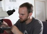 student peers into a microscope