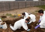 students in lab coats digging a hole