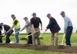 team of people shoveling in a field