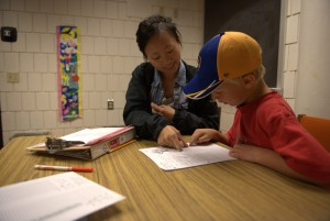 UW-Eau Claire psychology major Felicia Som works with seven-year-old Jack Barthen during a Summer Reading Program session.