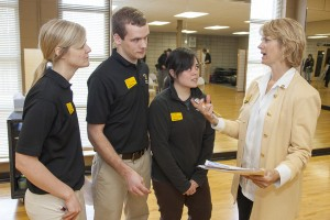 Students Chelsea Boesel (left), Adam Irwin and Francesca Paras talk withUWM's Carlynn Alt. Carlynn Alt, a clinical associate professor in the Department of Kinesiology in the College of Health Sciences, is a cancer survivor. She teaches students who work with cancer patients twice a week at Elite Sports Club in Glendale. Alt has found ways to use her own experience to inform her teaching and patient care. The work she and her students do is one of many examples of UWM's community engagement.