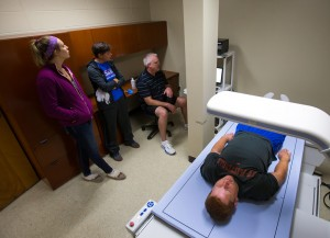 (from left to right): Abigail Fischer (biology major), Ryanne Breckenridge (certified athletic trainer), and Scott Soja (assistant professor in the department of health and human performance) performs a DXA scan on a UW-Platteville football player.
