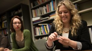 Social work students Joyce Idárraga, left, and Alissa Peanasky, right, look at the iPods they used for their research project examining the impact of personalized music on dementia caregivers.