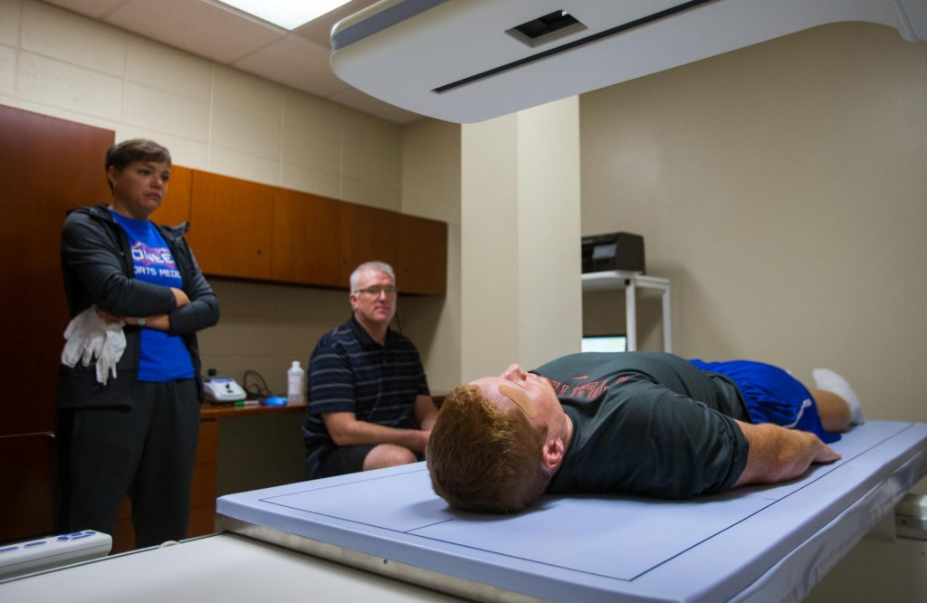 Scott Soja (sitting) performs a Dual Energy X-ray Absorptiometry (DXA) scan on a football player before a game to measure his muscle mass. Ryan Breckenridge (standing) is the team's head certified athletic trainer.