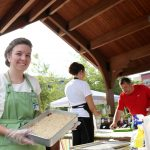 UW-Stout dietetics student Amanda Nass offers zucchini dessert squares at the Veggin' Out booth at the Downtown Farmers' Market in Eau Claire.