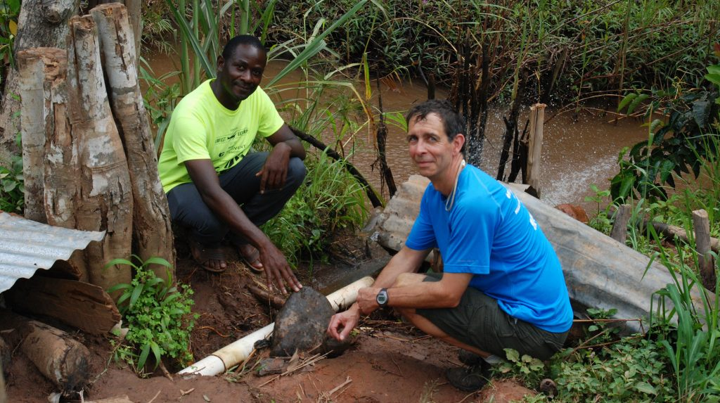 UW-Stout Professor Tom Lacksonen and Hastings Mkwandwire, a resident of Mzuzu, Malawi, observe one of Mkwandwire's hand-built hydroelectric generators under a metal covering.