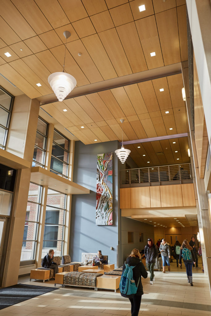 A combination of high efficiency lights and natural light have reduced energy consumption in Centennial Hall, UWL's academic building. In this picture the wall mounted sconce lights and the numerous recessed ceiling lights in the two-story gathering area work with the natural light sensors and timers to allow a large area to be lit while consuming less energy.