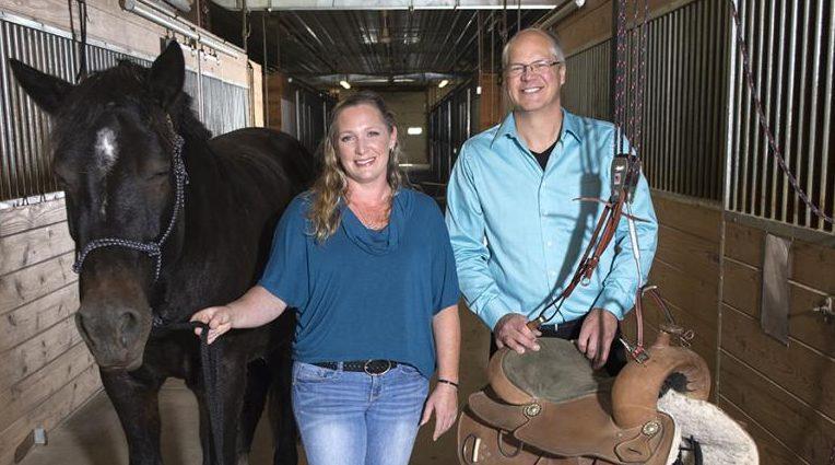 UW-River Falls student innovator Shanna Burris helps paraplegic horseback riders