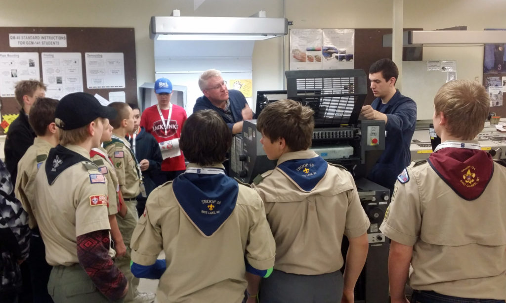 UW-Stout printing lab specialist Chad Nyseth, back left, and UW-Stout student Nick Egan demonstrate the use of a printing press to Boy Scouts during a merit badge class on campus.
