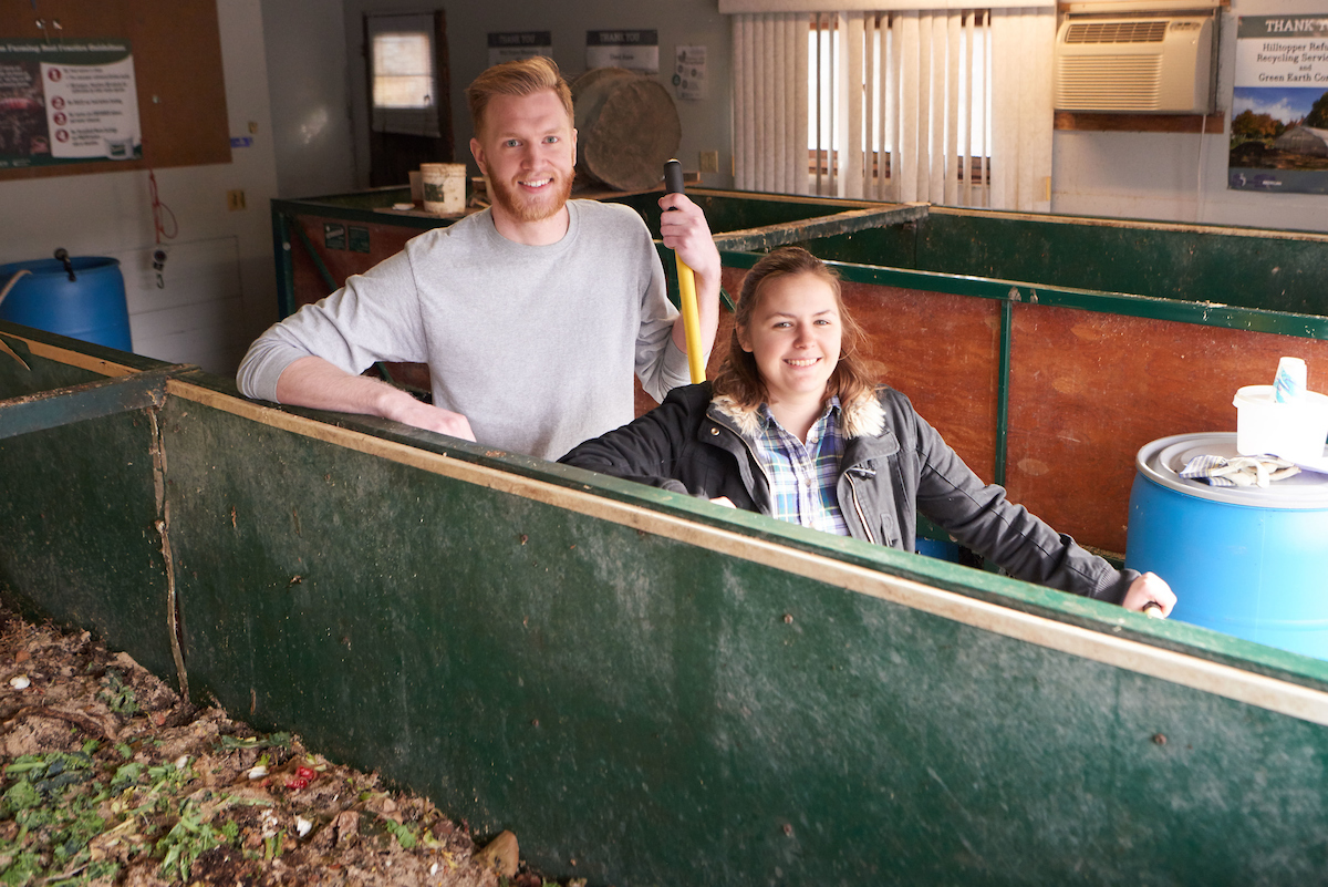 UW-La Crosse student Jeremy Shimetz and Andrea Schaefer, '16, stand by the vermicomposter, a 5 x 4 x 32-foot box that is home to tens of thousands of worms. Only pre-consumer food waste is added to the pile.