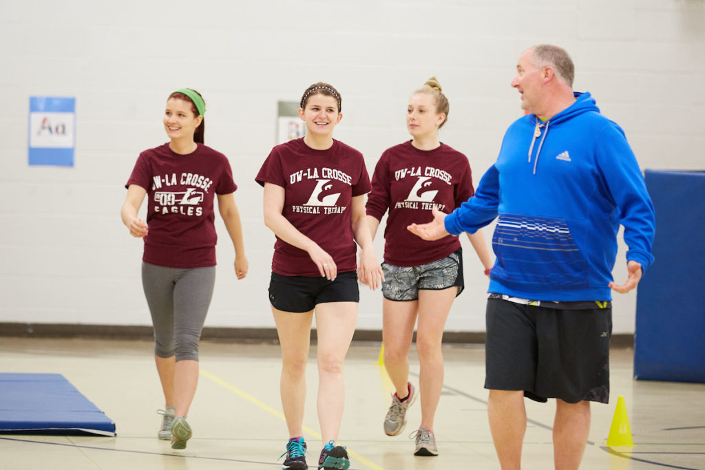 Physical Therapy graduate students, from left, Brenna Dubick, Abigail Bishop and Sydnie Kraus, take a warm up lap with Nicholas O'Keefe, physical education teacher at Summit Elementary School. The three UWL Physical Therapy students designed a fitness program at the La Crosse school along with student Elizabeth Skaer.
