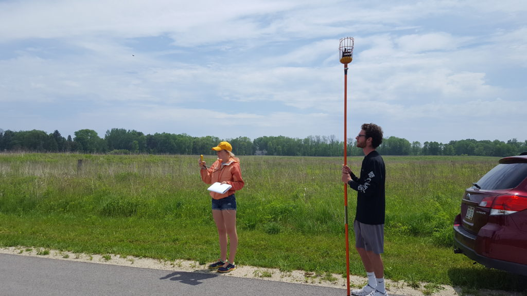 UW-Eau Claire students Molly McIlquham and Kyle Geib use an ozone monitor to measure the air at the same height at every stop during their fieldwork along Lake Michigan. They also record the local conditions, like temperature and wind speed, as measured by a hand-held weather meter.