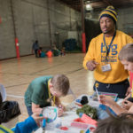 UW-Eau Claire student Ameer Collins, a participant in the Blugold Beginnings Learning Community, works with fifth-grade students from Manz Elementary School in Eau Claire during a citizenship and service event organized by the learning community members.