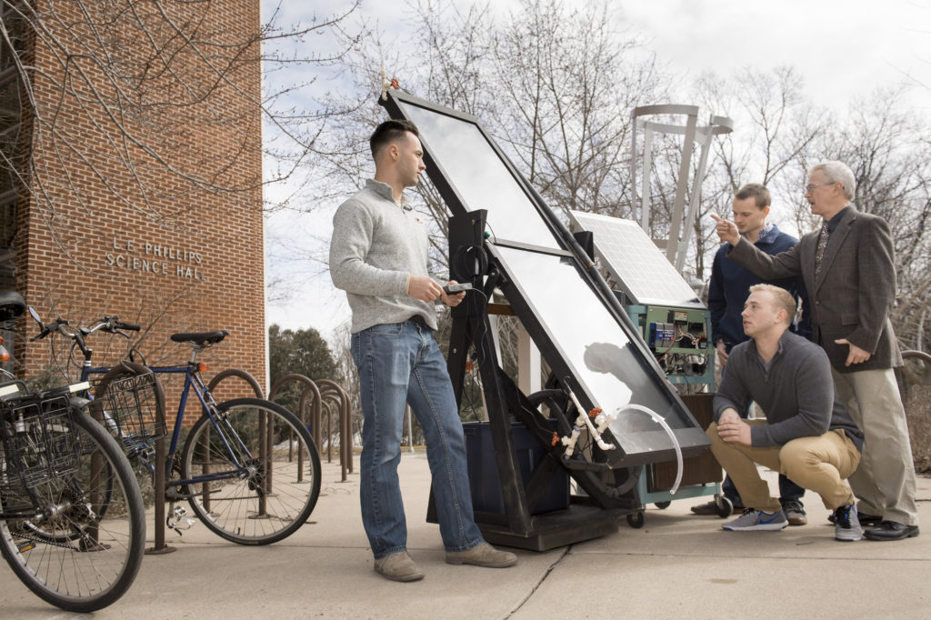 Dr. Kim Pierson, UW-Eau Claire professor of physics, discusses a solar-powered water heater he is developing with research students Brendon Kwick, Sawyer Buck and Hunter Hermes.