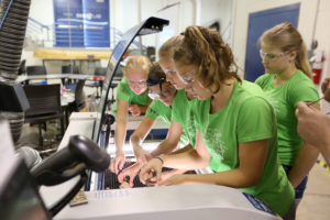 Girls place wood in a laser cutter at the Discovery Center Fab Lab on campus.