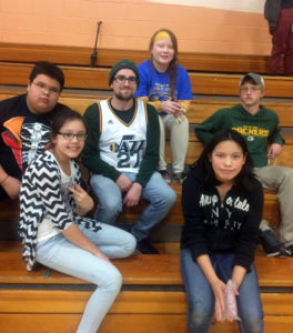 Noelle Metoxen, top, and fellow UW-Stout students Mike Firkins, third from left, and Matt Schmidt, right, take a break in the gym with Lac Courte Oreilles Ojibwe tribal school students.