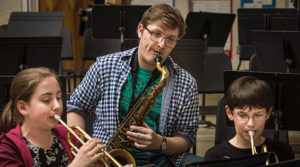 UW-River Falls music education student Kyle Punt, center, practices with Meyer Middle School sixth graders Claire Vaught, left, and Max Pnewski, right, during an afternoon Harmony Bridge session.