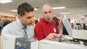 Photo of Carmine Savaglio, SC Johnson senior research scientist and UW-Parkside graduate, reviewing Shimadzu instrumentation with Shimadzu Field Service Engineer David Hobbs