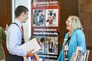 Barbara Nehls-Lowe, senior outreach specialist in the Division of Continuing Studies, talks with one of many corporate representatives, who ranged from human resource managers to CEOs and hailed from regional businesses and global companies. PHOTO: BRYCE RICHTER