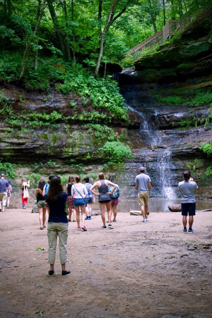 Photo of LAKES REU students at UW-Stout visiting Devil's Punch Bowl rock formation along the Red Cedar River near Menomonie.