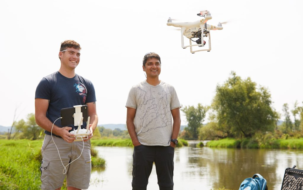 Photo of UW-La Crosse student Zachary Woodcock, left, who earned a summer research grant to use drones to conduct aerial surveys of purple loosestrife, an aquatic invasive plant with help from UWL faculty mentor and remote sensing scientist, Niti Mishra, right. Here Woodcock takes a drone survey test flight at the La Crosse River Delta near Bangor, Wisconsin.