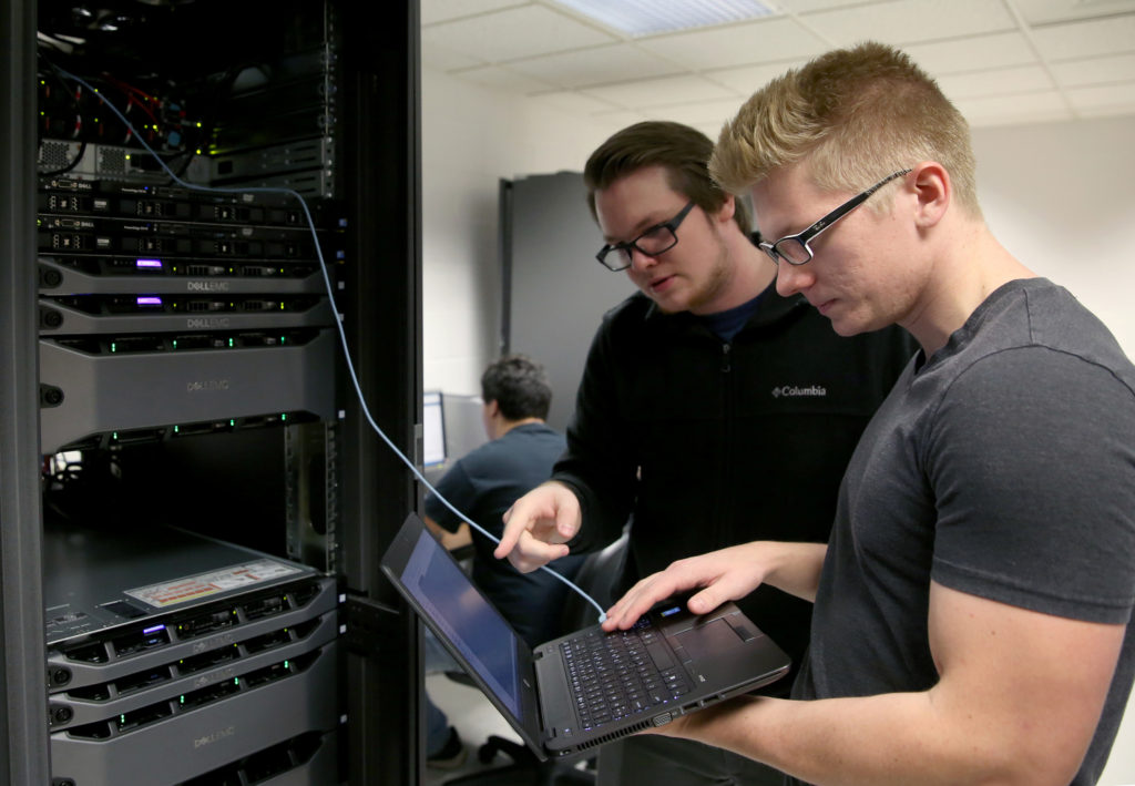 Photo of UW-Stout students Pierce Lannue, left, and Stephen Felton, who are working in a computer networking and information technology lab in October in Fryklund Hall. UW-Stout has been named a national Center of Academic Excellence in Cyber Defense.
