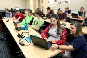 Photo of Professor Diane Christie, right, helping students in a Computer Science I class in September at UW-Stout, which has been named a national Center of Academic Excellence in Cyber Defense.