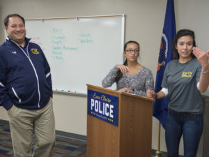 Photo of Dr. Jeff Janot and Blugolds Chantal Bougie and Anna Kohler (from left) talking with Eau Claire police officers about a shared research project.