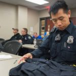 Photo of Mark Vang, an officer with the Eau Claire Police Department, who is looking at a vest he will wear as part of a research project with UW-Eau Claire kinesiology students and faculty to determine if the vests will help ease back pain among police officers.