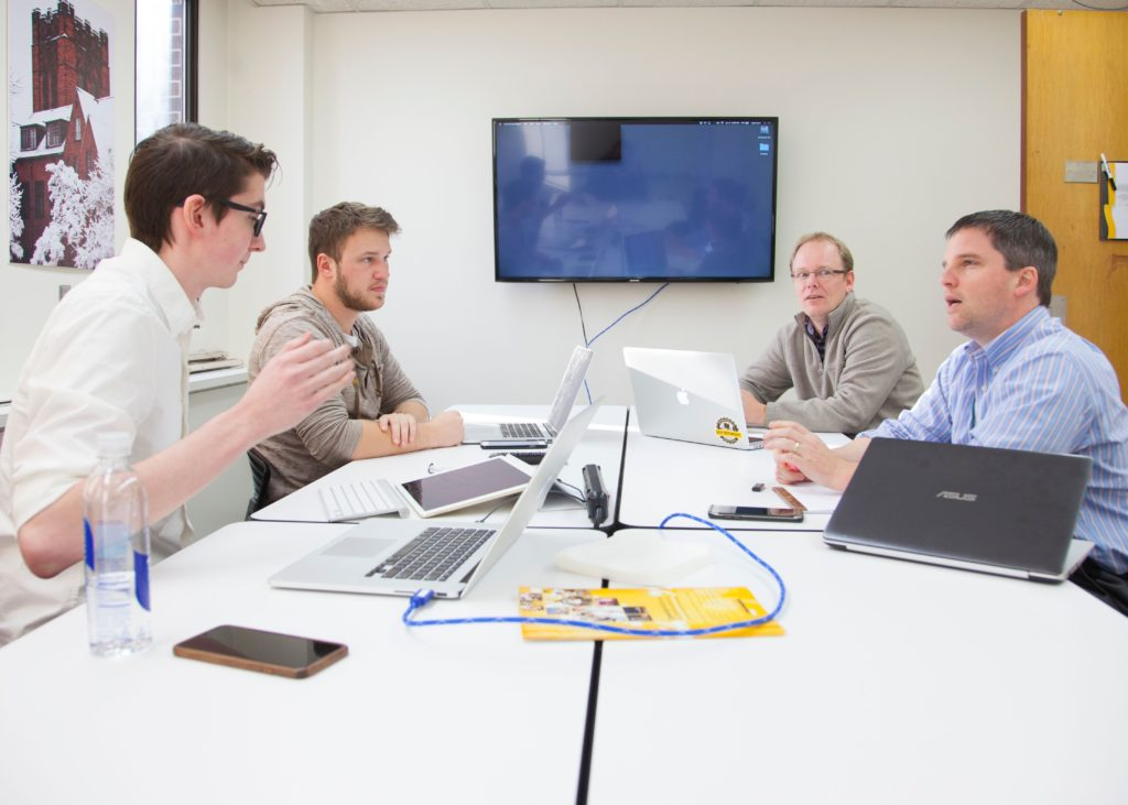 Photo of students in UWM's App Brewery working with doctors at the Medical College of Wisconsin to develop an app that helps guide doctors during the delicate process of brain surgery.