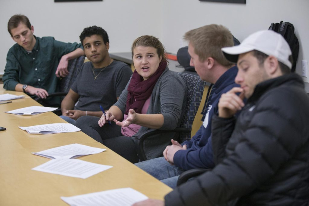 Photo of (from left) students Ron Tittle, Alexandre Vieira, Taylor Griffith, Mark Ellis and Alejandro Esquivel, practicing their discussion and analysis of economic indicators in a classroom at Hyland Hall on Monday, November 20, 2017.