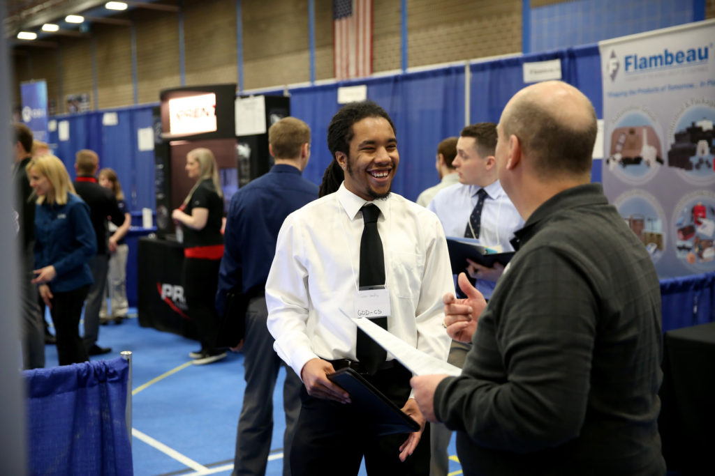 Photo of Jalen Hendley, a computer science-game design major from Flossmoor, Ill., visiting with a recruiter at a 2017 Career Conference. / UW-Stout photo by Brett Roseman