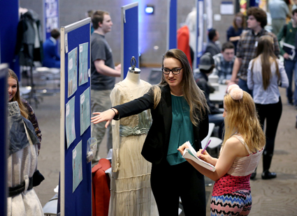 Photo of Sofia VanTassel, an apparel design and development major, explaining her research on the history of clothing at the STEMM Student Expo Dec. 14 at UW-Stout.