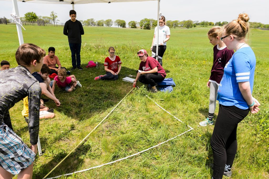 Photo of recent UW-Madison alumna Sarah Taylor, squatting at center, and Aleesha Kozar, standing at center, demonstrating a method for accurately measuring square grids of land as groups of sixth graders visiting from Fort Atkinson Middle School tour one of four educational stations temporarily set up at Aztalan State Park, a prehistoric Native American site located near Lake Mills, Wis., during spring on May 24, 2018. Funded by a Baldwin Wisconsin Idea Project Grant, the public outreach program is led by UW-Madison Anthropology Professor Sissel Schroeder, who has previously conducted several undergraduate archeological fields schools and research projects at the site. (Photo by Jeff Miller / UW-Madison)