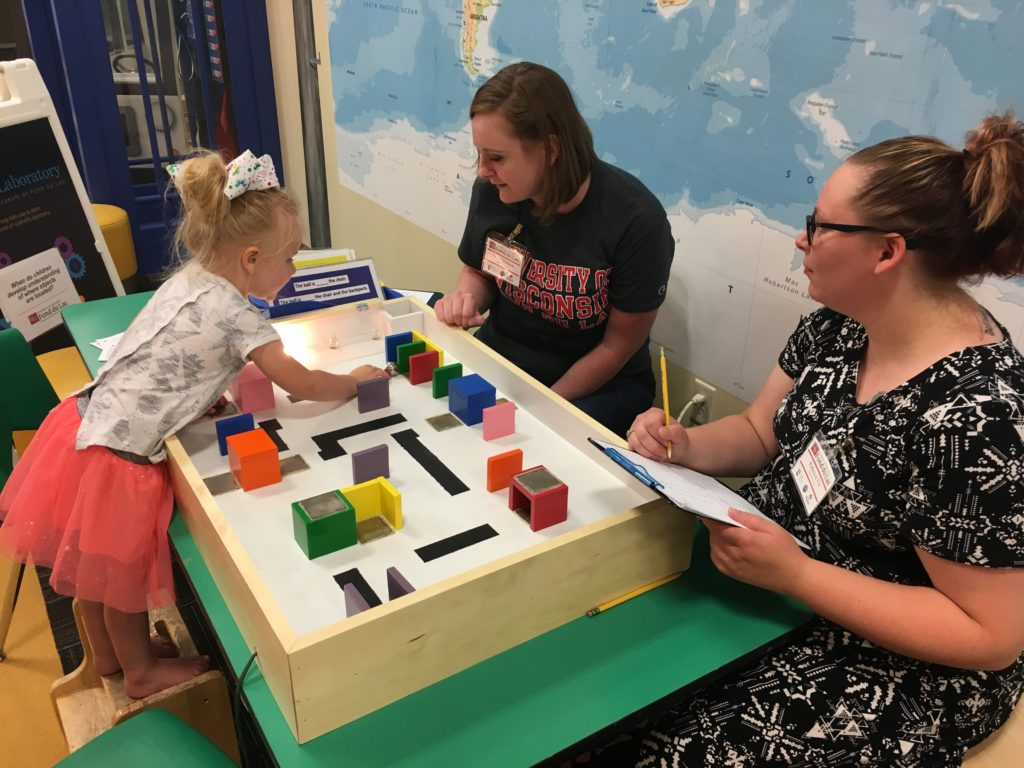Photo of Clara Wojkiewicz (left) participating in an activity at the Children's Museum of Fond du Lac while UW-Fond du Lac students Grace Hudson (center) and Becky Vis (right) monitor her progress.
