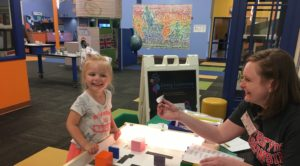 Photo of Clara Wojkiewicz (left) participating in an activity at the Children's Museum of Fond du Lac while UW-Fond du Lac student Grace Hudson monitors her progress.