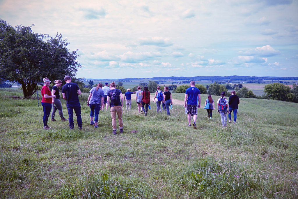 Photos of students walking in a pasture in Dunn County to learn more about the soils and farming in the area. The LAKES REU students shared their summer research on Aug. 8 in Menomonie, and Aug. 10 in Chetek.