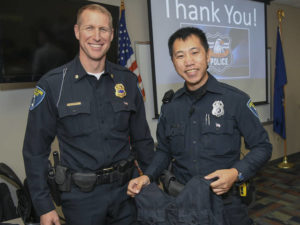 Photo of Matt Rokus, deputy chief of police, (left) issueing Eau Claire police officer Mark Vang his load-bearing vest.