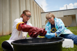 Photo of UWL graduate student Anna Hilger and her faculty mentor, Bonnie Bratina, UWL associate professor of Microbiology, setting up containers outdoors where they introduced a mix of marsh water and sediment, as well as crude oil to mimic a potential oil spill.