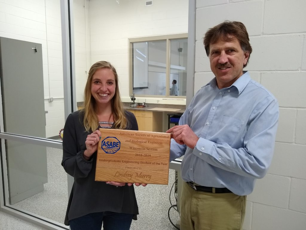 Photo of Joe Shakal, chair of the Agricultural Engineering Technology Department at UW-River Falls, presenting senior Lindsey Murry with the 2019 ASABE Agricultural Engineering Undergraduate Student of the Year Award.