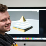Photo of an art student in a digital fabrication class, who recently gained real-world professional experience working with one of the community's most prestigious employers, Oshkosh Defense.