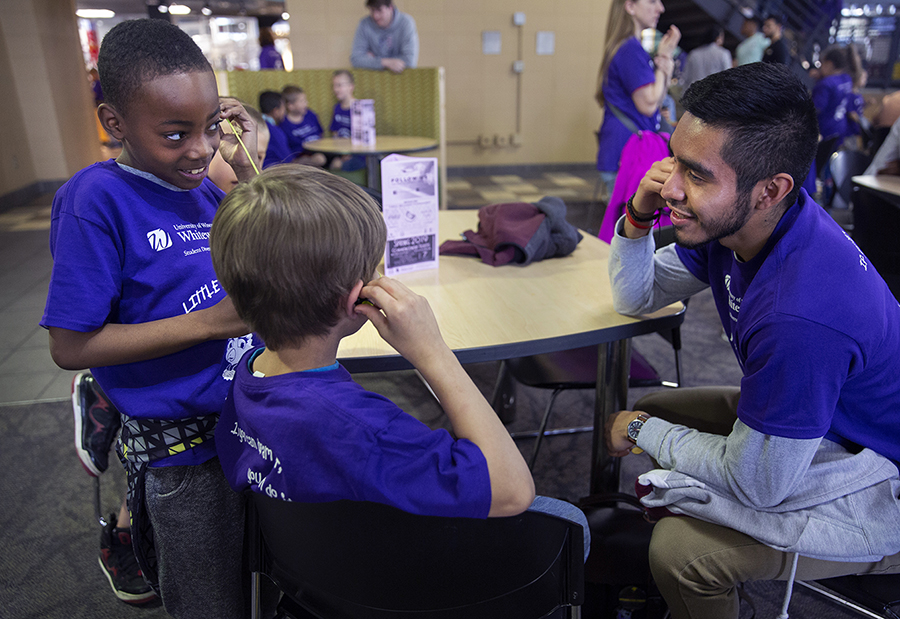 Photo of Beloit Wis., second graders in the Little Scholars Program visiting their UW-Whitewater college student pen pals. UW-Whitewater finance student Miguel Miranda, right, lets children try his bluetooth earbuds at lunch. A valuable exchange of friendship came to campus on Wednesday as children from Converse Elementary School in Beloit visited their UW-Whitewater student pen pals. The Budding Scholars Program in the office of Student Diversity, Engagement and Success pairs university students with a second or third grader from Converse. The children practice their writing skills in letters and learn about higher education. The university students visited Converse in December: on Thursday, the Converse students returned the visit. The program was started in 2015 with a King/Chavez Scholar class and expanded to include New Student Seminar classes and the Future Teacher Program. (UW-Whitewater photo/Craig Schreiner)