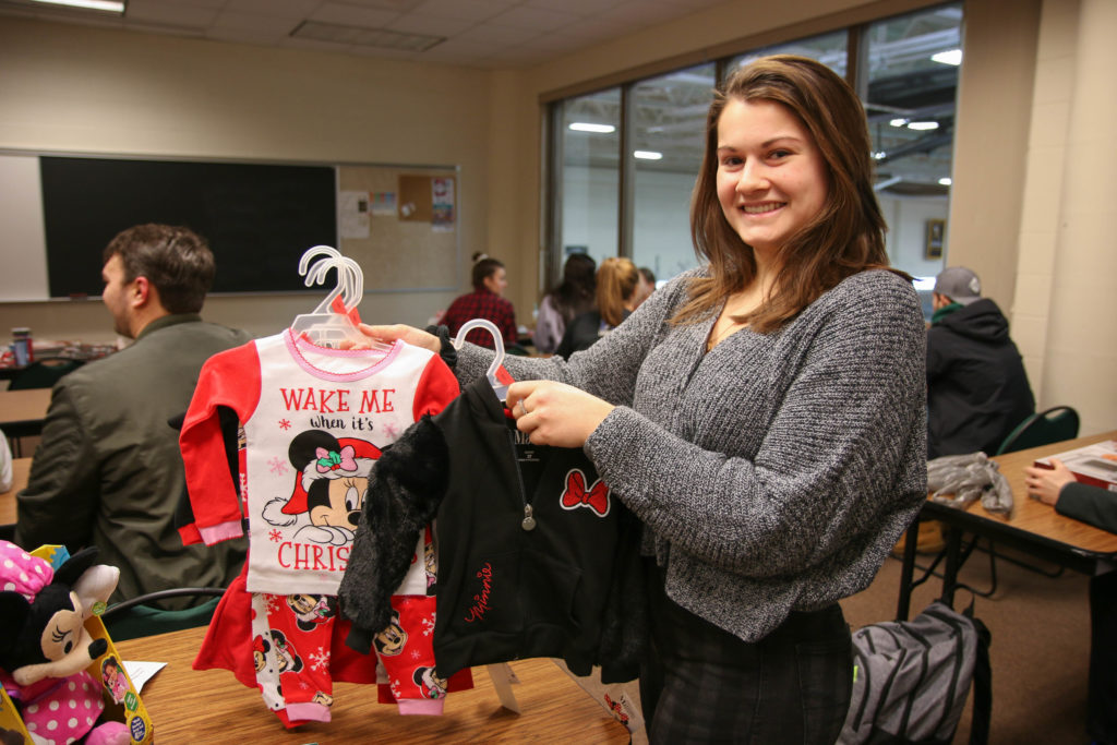 Photo of a UW-Superior student-athlete holding up children's clothes for the university's Giving Tree