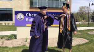 Photo of Chancellor Bernie Patterson and a 2020 spring graduate giving a congratulatory elbow bump