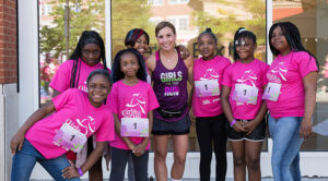 """Photo of Tina Jones, executive director of Girls on the Run of Southeastern Wisconsin, standing with some of the kids involved in the program. """"What I love about this organization is that we are there to build strong girls and look at the whole girl,"""" she said. """"It's not just the physical component of things, it's the emotional component and the social component."""" (Photo courtesy of Tina Jones)"""