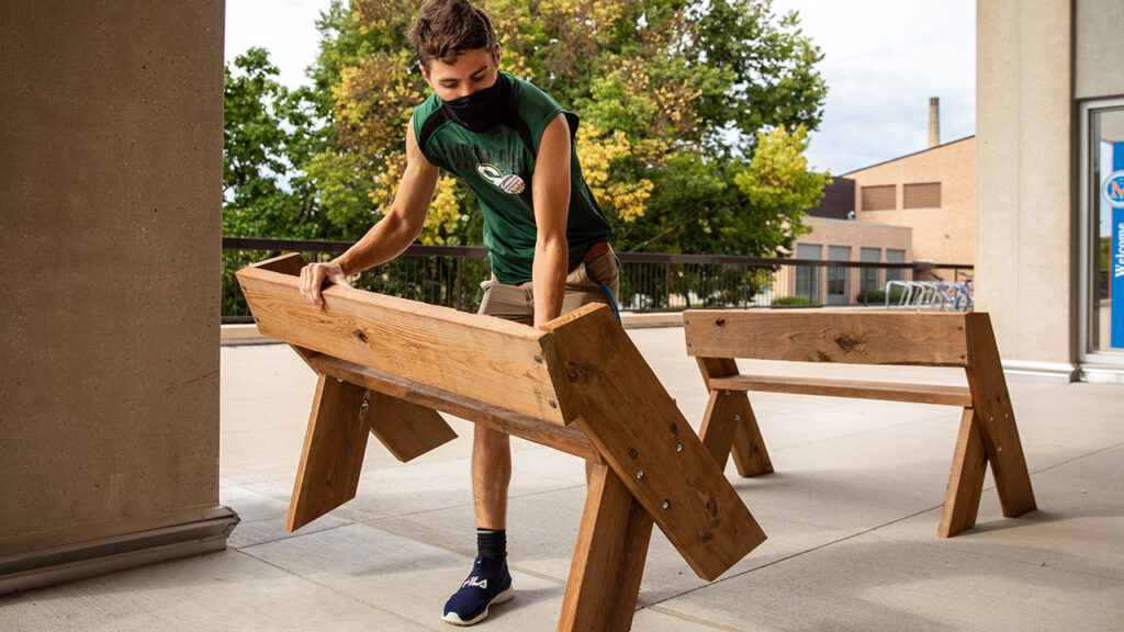 Photo of UW-Platteville student volunteer carrying a bench to set up an outdoor classroom during the COVID-19 pandemic