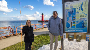 Photo of UW-Milwaukee faculty members Kim Beckmann and John Janssen showing off the results of their joint project, a map of the aquatic ecology of the Milwaukee harbor. A host of environmental agencies are using it to help them make decisions about what restoration projects they will undertake. (UWM Photo/Troye Fox)