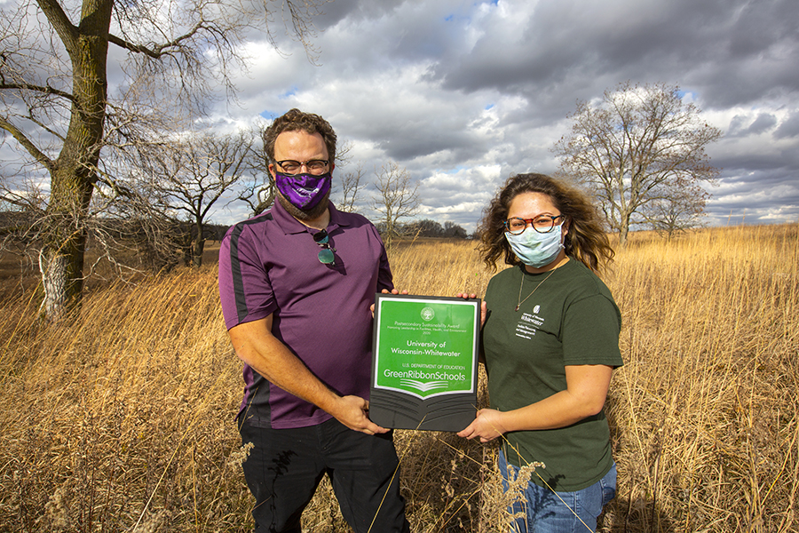 Photo of UW-Whitewater Sustainability director Wes Enterline, left, and assistant coordinator Ashley Flor showing the Green Ribbon Schools plaque awarded to the university by the U.S. Department of Education. The award honors leadership in facilities, health and environment on the campus. (UW-Whitewater photo/Craig Schreiner)