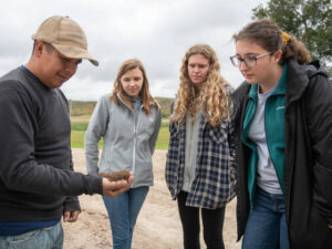 Photo of Farm worker Roberto Montalvo (left) talking with Blugolds Grace Johnson, Amanda Cassin and Bethany Johnson during the students' visit to a western Wisconsin farm.